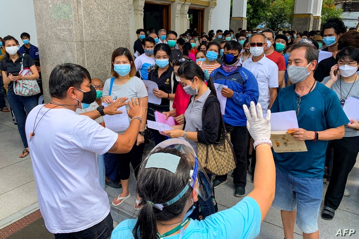 People wait to be inoculated with a dose of a Covid-19 coronavirus vaccine at the Holy Redeemer Catholic church in Bangkok on...