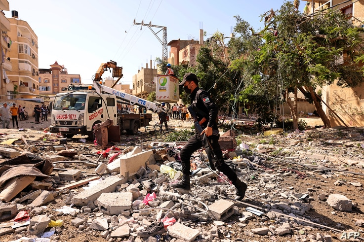 A member of the Palestinians Hamas security forces walks in the midst of damage caused by an Israeli air strike in the town of…