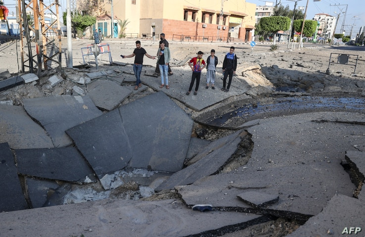 Palestinian youths take pictures with their smart phones of a huge crater on a main road in Gaza City on May 13, 2021 following…
