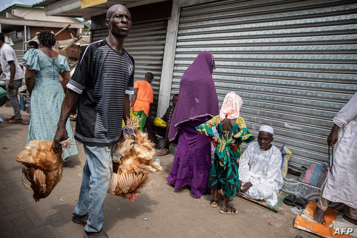 A man carries chickens for sale in a market  in Accra, Ghana, on May 13, 2021 during Eid Al-Fitr prayer that marks the end of…