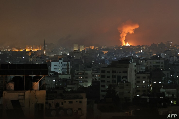 An explosion lights the sky following an Israeli air strike on Beit Lahia in the northern Gaza Strip on May 14, 2021. (Photo by...