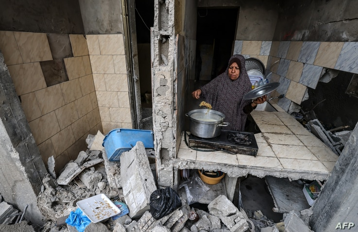 TOPSHOT - A Palestinian woman who has returned to her neighbourhood, cooks a meal in what remains of her home, hit by Israeli…