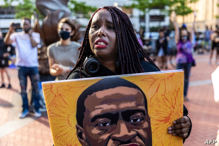 A woman reacts as she marches during an event in remembrance of George Floyd in Minneapolis, Minnesota, on May 23, 2021. -…