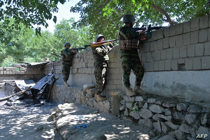 Members of Afghan security forces take their positions during an ongoing clash between Taliban and Afghan forces in Mihtarlam,…