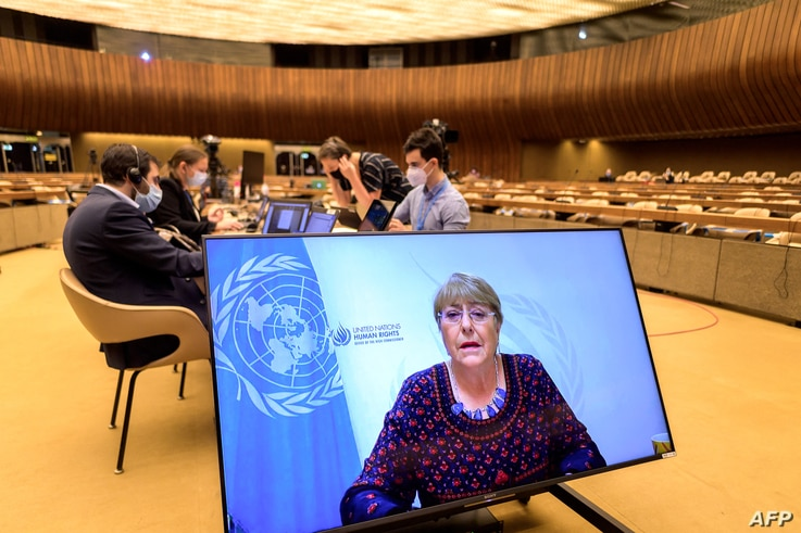 United Nations High Commissioner for Human Rights Michelle Bachelet is seen on a screen delivering her speech remotely at the…