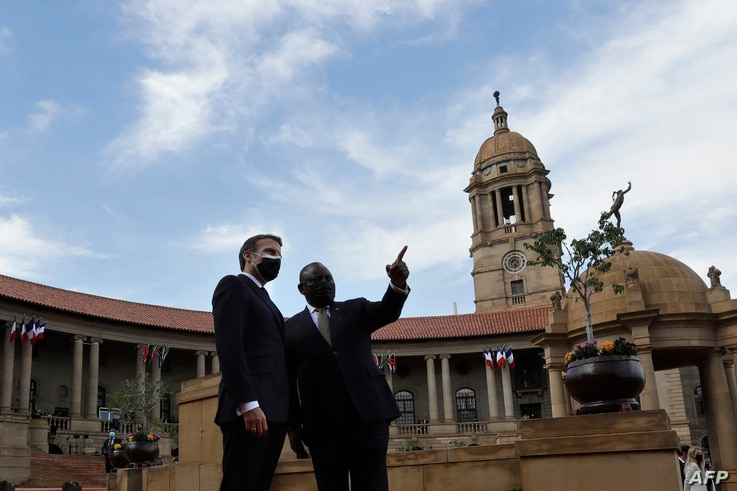 South African President Cyril Ramaphosa (right) and his French counterpart Emmanuel Macron speak at a welcoming ceremony at the…