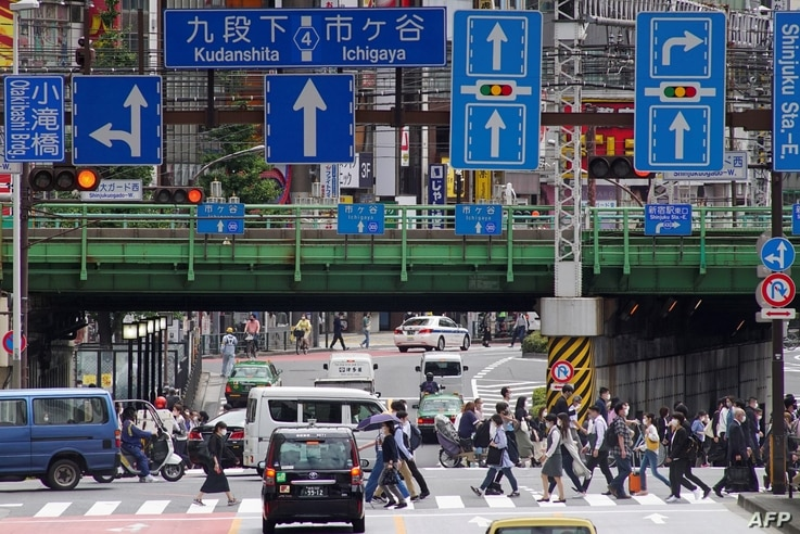 Commuters walk near Shinjuku Station in Tokyo on May 31, 2021 after the announcement that the governemrnt extended a…