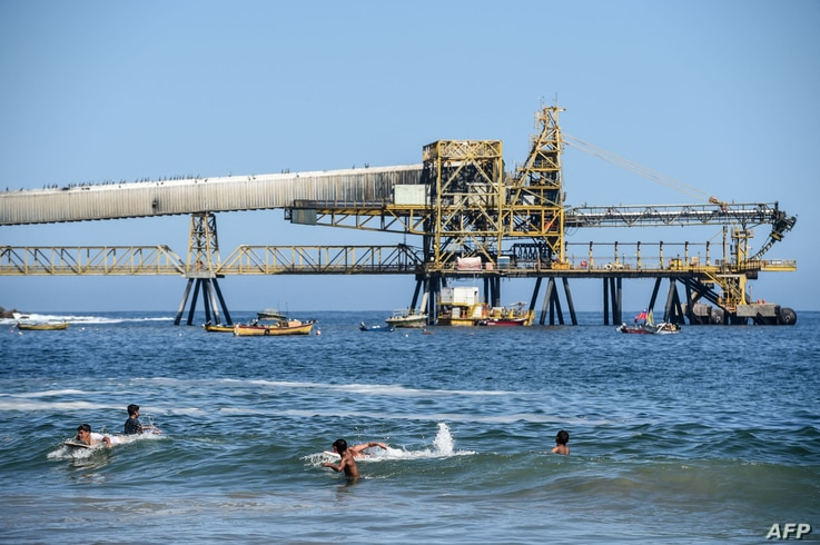 """People cool off in the beach near the mining pipeline """"Puerto Coloso"""" of the """"Escondida"""" cooper mine, responsible for loading…"""