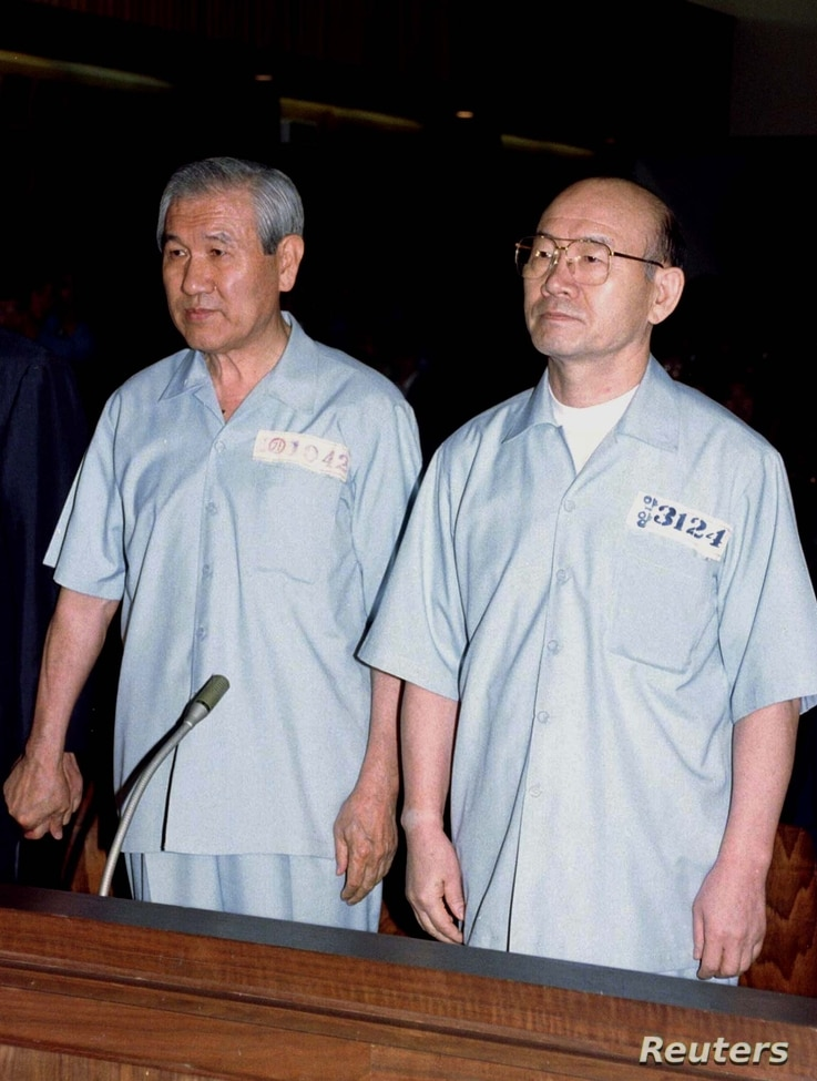 Former South Korean presidents Chun Doo Hwan (R) and Roh Tae Woo (L), dressed in jailhouse uniforms, face a panel of judges at…