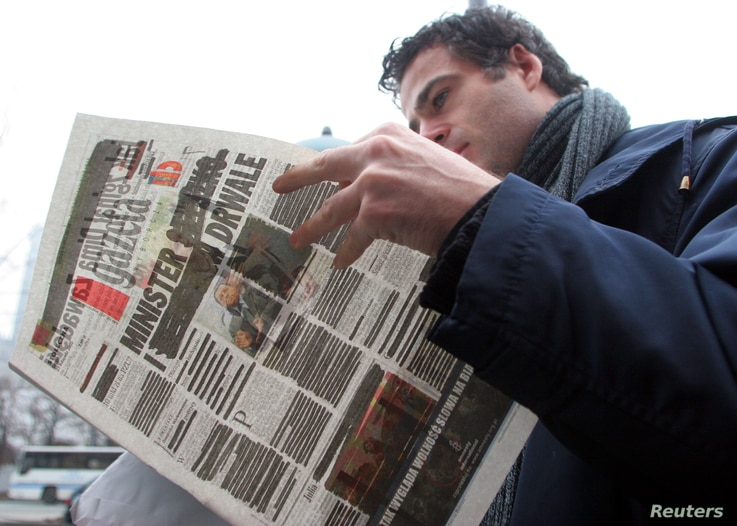A man reads the Polish daily newspaper Gazeta Wyborcza in the centre of Warsaw November 23, 2005. Two leading Polish daily...