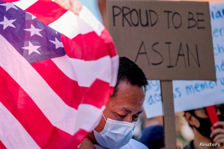 A demonstrator stands between a U.S. flag and a sign during a rally against anti-Asian hate crimes in Los Angeles.