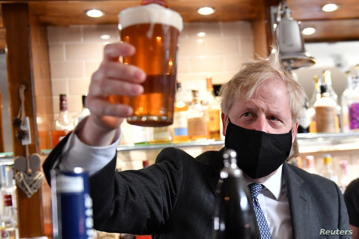 Britain's Prime Minister Boris Johnson holds up a pint during a visit to The Mount Tavern Pub and Restaurant on the local…