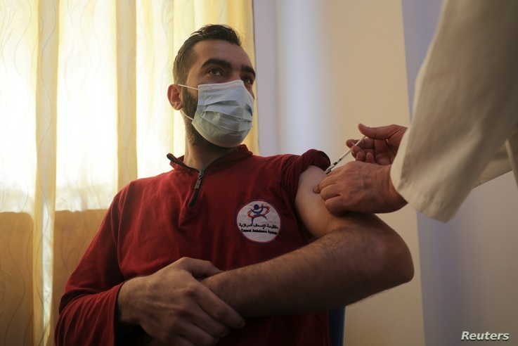 A man receives a dose of the coronavirus disease (COVID-19) vaccine at a hospital in Idlib, Syria, May 1, 2021. REUTERS/Khalil...