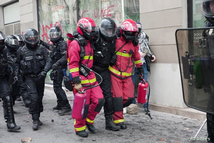 Firefighters carry police officer away from clashes during the traditional May Day protests, amid the coronavirus disease …