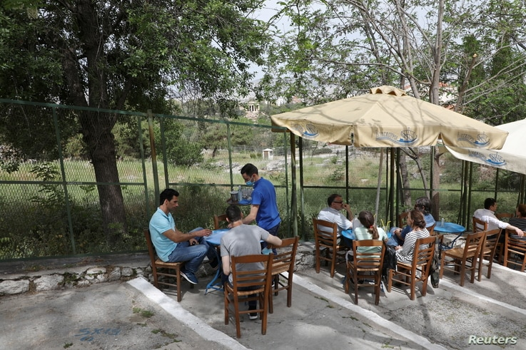A waiter serves a group of people at a restaurant in the Plaka district, while restaurants and cafes in Greece open after six months ...