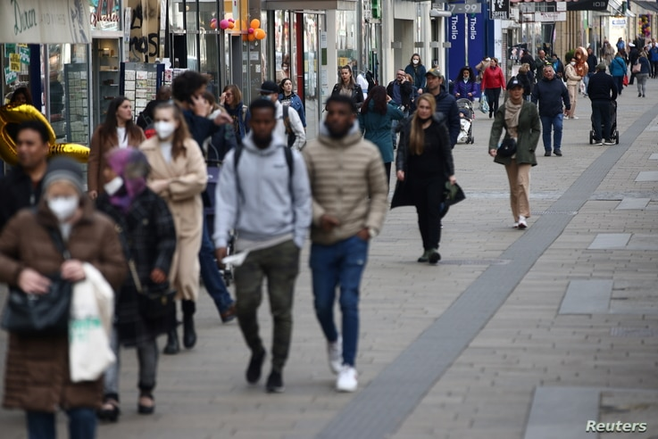 People walk along a shopping street as shops reopened after lockdown was loosened during the coronavirus (COVID-19) pandemic in…