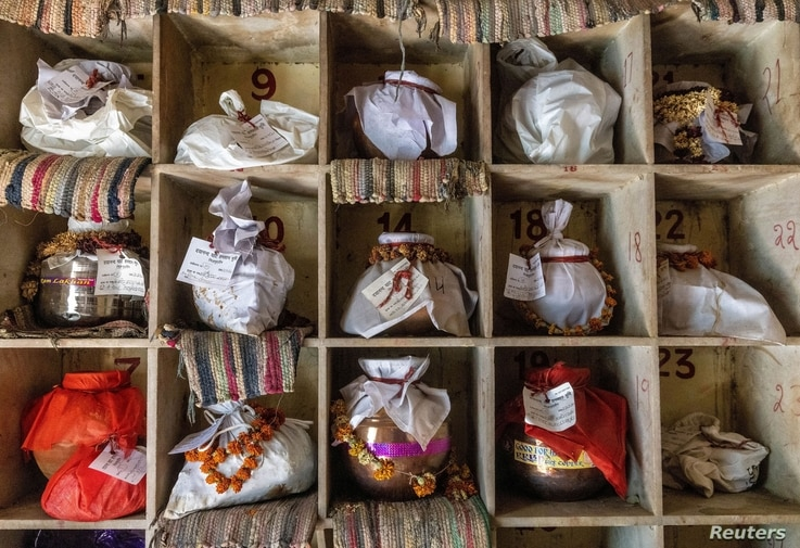 Urns containing ashes after final rites of people including those who died from the coronavirus disease (COVID-19) await…