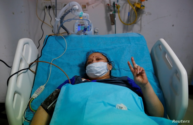 Geetika, 45, who is suffering from coronavirus disease (COVID-19), gestures as she receives treatment inside the emergency room…