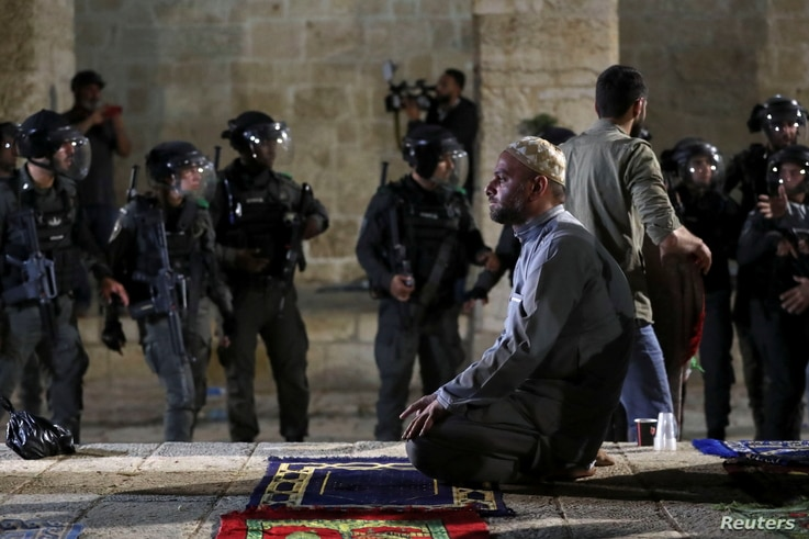 A Palestinian man prays as Israeli police gather during clashes at the compound that houses Al-Aqsa Mosque, known to Muslims as...