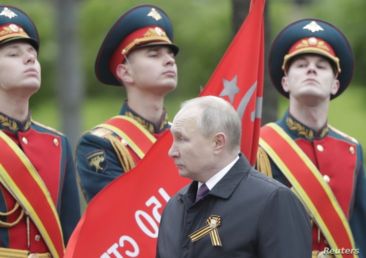 Russian President Vladimir Putin takes part in a commemoration ceremony at the Tomb of the Unknown Soldier on Victory Day,…