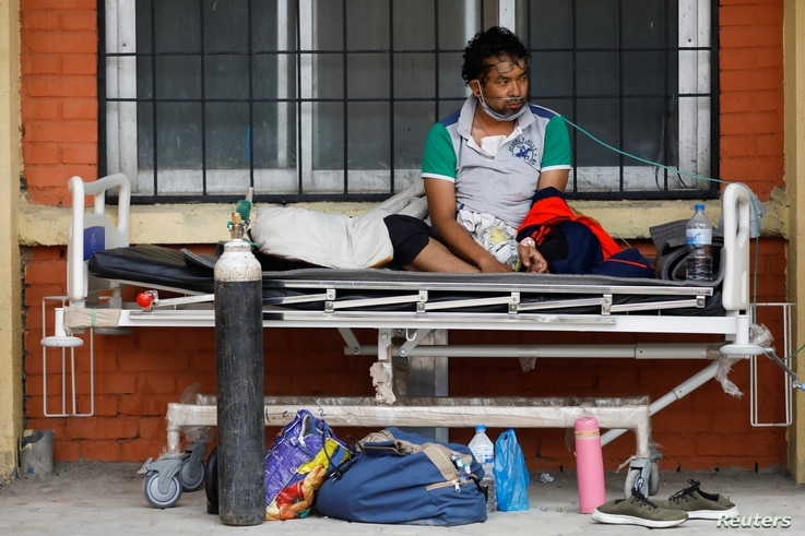 A patient receives oxygen as he waits outside the passage of a hospital due to a lack of free beds inside the hospital for coronavirus disease (COVID-19) patients, as the second major coronavirus wave surges in Kathmandu, Nepal, May 10, 2021.
