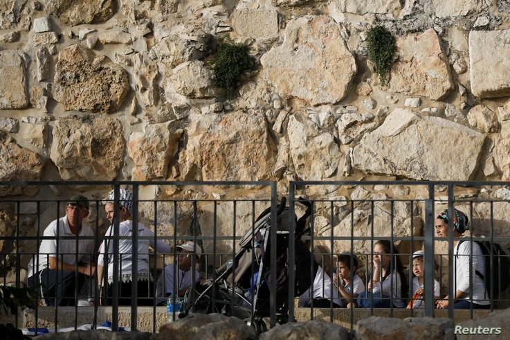 People take cover as a siren sounds warning of incoming rockets, amid Israeli-Palestinian tension, on Jerusalem Day, near the…