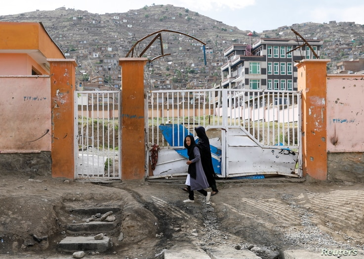 A woman with a girl walks past the site of a car bomb blast that targeted schoolgirls in Kabul, Afghanistan May 10, 2021…