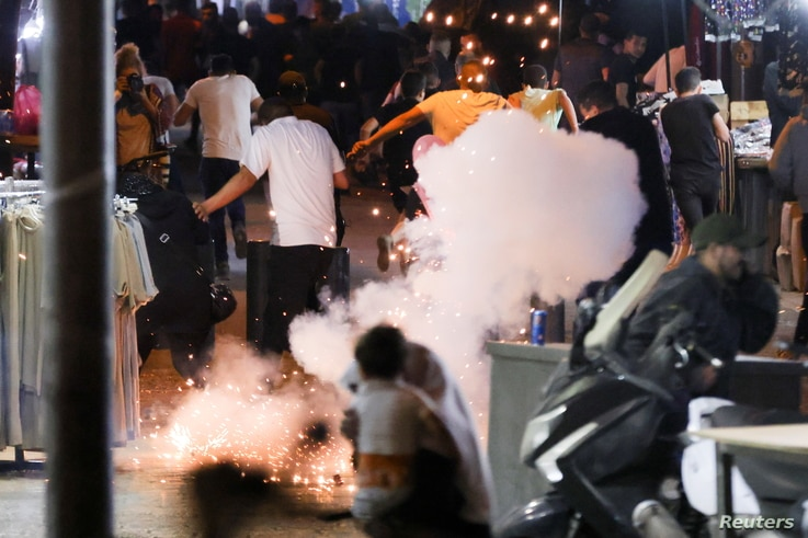 Palestinians disperse as a stun grenade fired by Israeli security forces explodes near Damascus Gate just outside Jerusalem's Old City May 10, 2021.