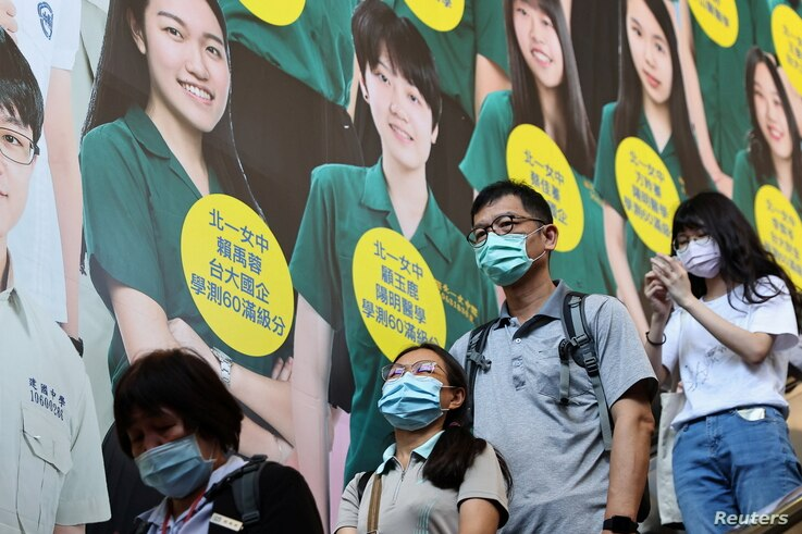 People wear protective face masks while heading in a metro station following the outbreak of coronavirus disease (COVID-19),...