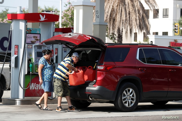 A man loads a 5 gallon gas tanks in his car after filling multiple of them up at a Wawa gas station, following a cyberattack...