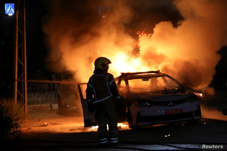 An Israeli firefighter stands near a burning Israeli police car during clashes between Israeli police and members of the...