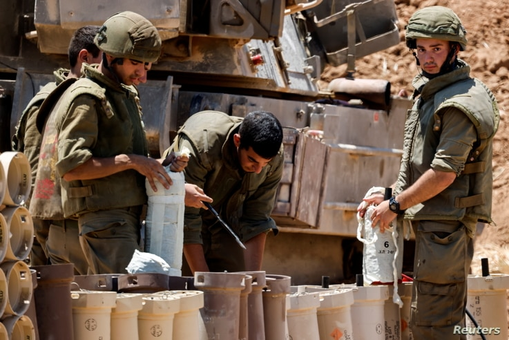 Israeli soldiers check artillery shells in an area near the border with Gaza, in southern Israel May 13, 2021. REUTERS/Amir…