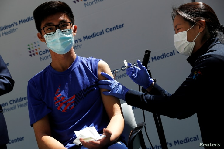Thomas Lo (15) receives a dose of the Pfizer-BioNTech vaccine for the coronavirus disease (COVID-19) at Northwell Health's…