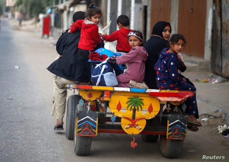 Palestinians ride on a donkey-drawn cart as they flee their homes during Israeli air and artillery strikes, in the northern…
