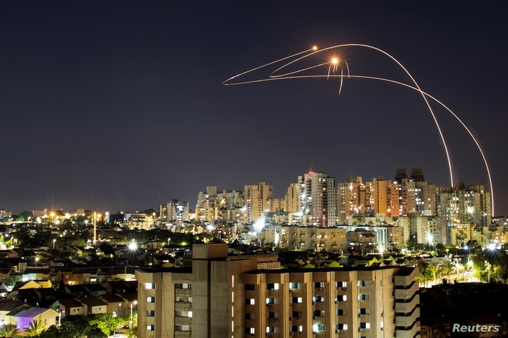 Streaks of light are seen as Israel's Iron Dome anti-missile system intercepts rockets launched from the Gaza Strip towards…