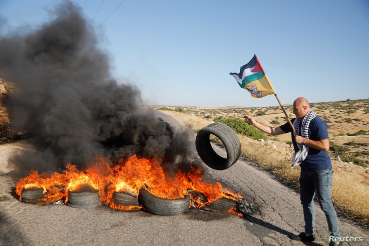 A Palestinian demonstrator throws a tire to a burning barricade, following a flare-up of Israeli-Palestinian violence, on a…