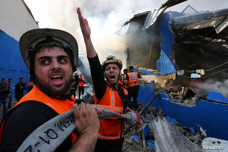 A Palestinian firefighter reacts as he participates in efforts to put out a fire at a sponge factory after it was hit by…