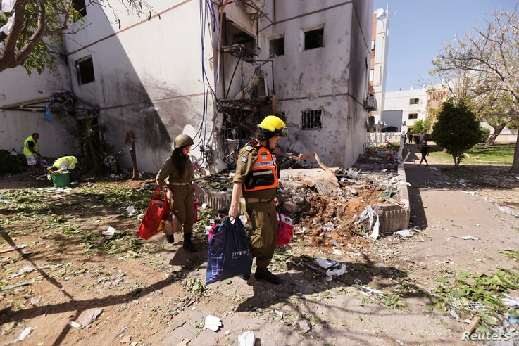 Soldiers help to carry residents' personal belongings out of a damaged building following a rocket attack from Gaza, in Ashdod, Israel, May 17, 2021.