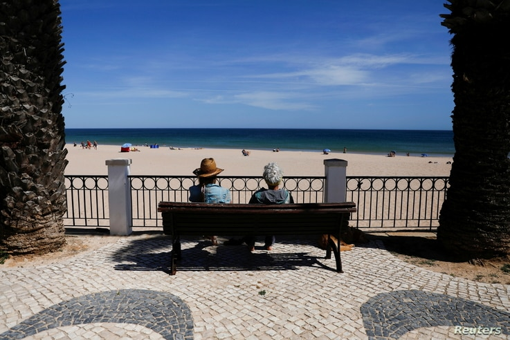 People look at Luz beach on the first day that Britons are allowed to enter Portugal without needing to quarantine, as…