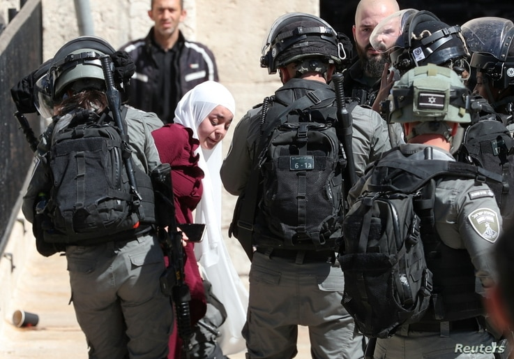 Israeli security force members detain a Palestinian woman during a demonstration held by Palestinians to show their solidarity…
