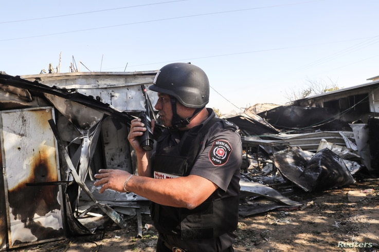 An Israeli fire and rescue personnel member works at the scene where a rocket launched from the Gaza Strip landed, causing…