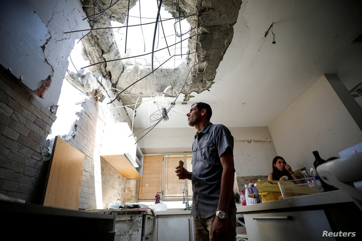Adi Vaizel, looks at the damage caused to the kitchen of his house after it was hit by a rocket launched from the Gaza Strip…