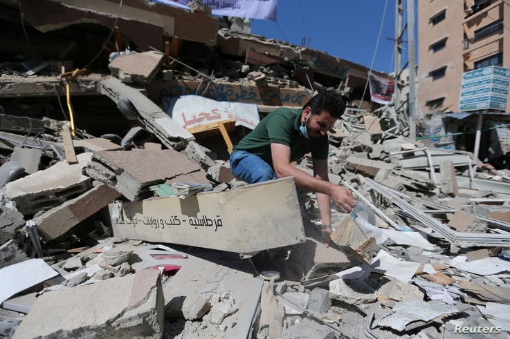 Palestinian Shaban Esleem inspects the rubbles of his bookstore which was destroyed in Israeli airstrikes during the Israeli-Palestinian fighting, in Gaza City, May 24, 2021.