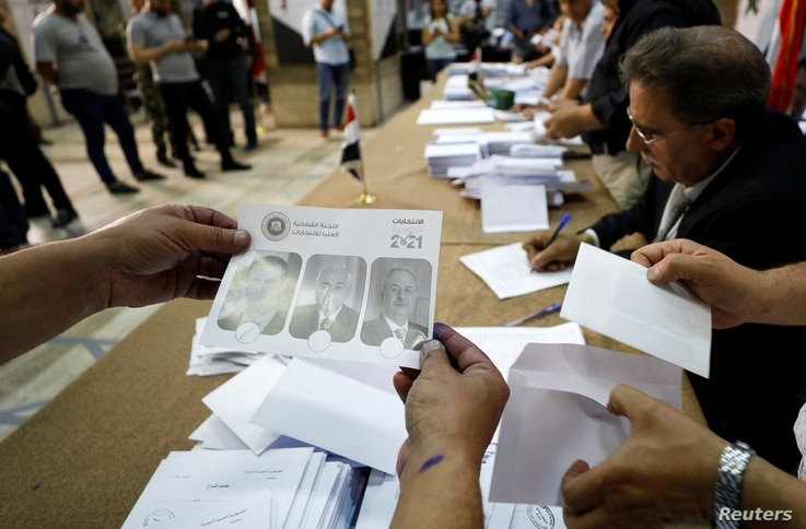Poll workers count ballots after polls closed during the country's presidential elections in Damascus, Syria, May 27, 2021...