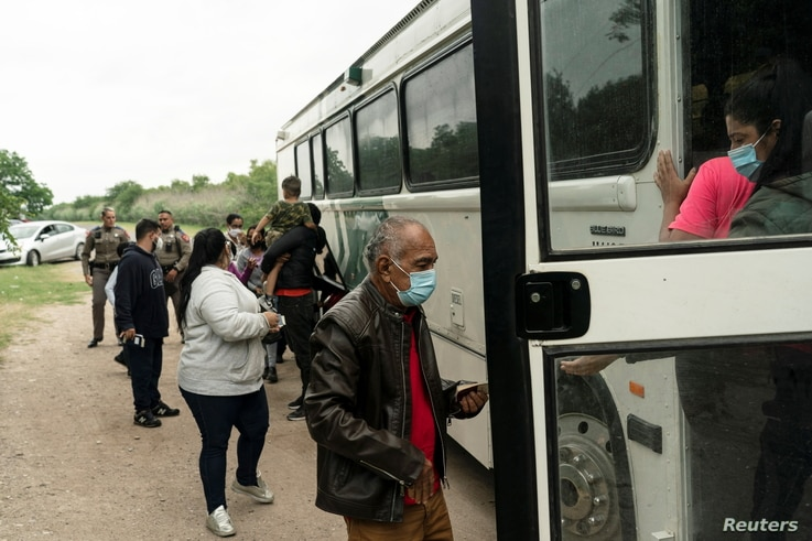 Asylum-seeking migrants' families from Venezuela board an U.S. Border Patrol's bus to be transported after crossing the Rio...