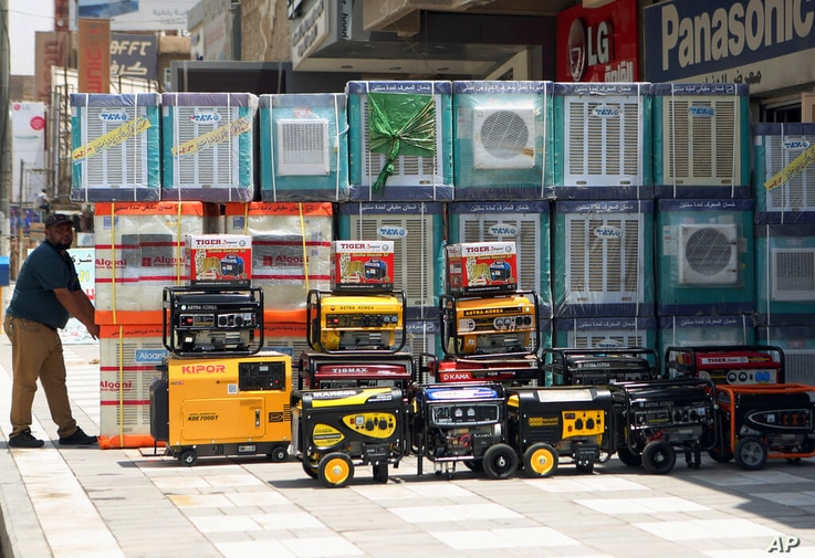 FILE - In this Thursday, July 30, 2015 file photo, air conditioners and power generators are displayed on a street in central…