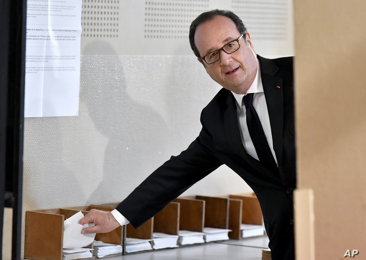 French president Francois Hollande picks up ballots before voting in the first round of the presidential election in Tulle,…