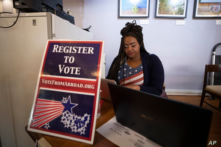 Le' Ana Freeman from Washington registers before casting vote on the Super Tuesday for U.S. Democrats Abroad multi-location...