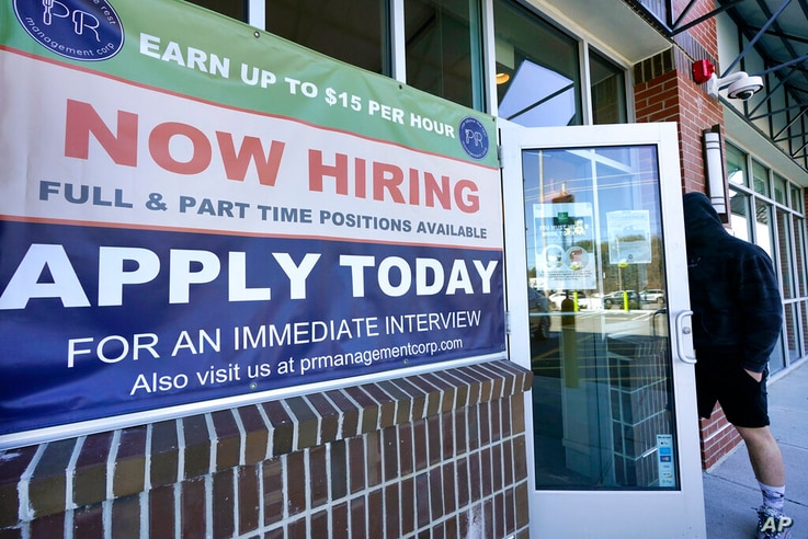 A man walks into a restaurant displaying a 'Now Hiring' sign, Thursday, March 4, 2021, in Salem, N.H. U.S. employers added a...