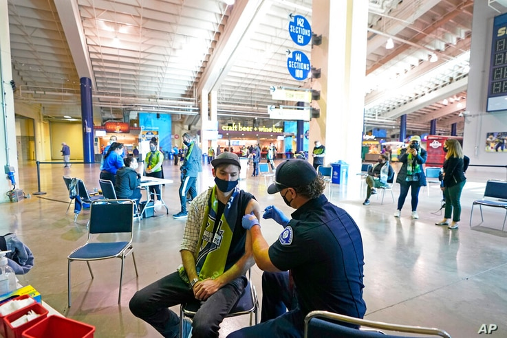 FILE - In this May 2, 2021, file photo, Austin Kennedy, left, a Seattle Sounders season ticket holder, gets the Johnson &...